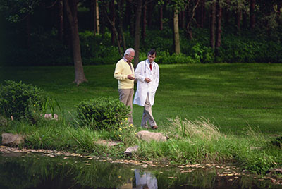 senior and doctor walking along side a pond